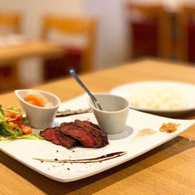 周南のおすすめ人気ランチ特集  ◆ (肉)24ニイヨン [周南市 ランチ] 今回ご紹介するランチは、周南市PH通りにオープンした美味しい和牛が味わえるお店「(肉)24ニイヨン」さんです♪ 6月24日にオープンし、約1ヶ月は夜だけの営業でしたが、なんと7月20日からランチスタート♪ それは行くしかないでしょ! てな感じで行ってきました!!  レトロチックな入口を入ると中は女子好みのオシャレな空間。コンクリート打ちっぱなしの壁には24の文字も書かれてどこかかわいい♪ そんな中を通り、M子は一番奥の席に案内され、ランチ-オープン初日で他にもお客さんがいましたが、各グループと適度に離された感じに席は取り、コロナ対策もバッチリ! そういえば入口にアルコール消毒も置いてありました。  ここニイヨンさんのおすすめ和牛を食しないと! との思いだったので、悩むことなく数量限定の「ニイヨン ハラミランチ」を注文。  ■ハラミステーキ■ライス■サラダ■スープ■ドリンク  という内容。  M子、そういえば前回のランチレポートもステーキだったような......。 前回はサガリステーキ、今回はハラミステーキ。 似たような名前ですが、部位もほとんど一緒で、ハラミの方が若干脂肪が多い。赤身でジューシーお肉の濃い味がするってことは前回もお話ししたように同じです。  ニイヨンさんのハラミステーキは、特製のステーキソースも添えられてますし、岩塩とにんにくチップも用意されてます。 自分の好みにアレンジできるようになっていて、M子は甲乙つけがたいほど、ソースも岩塩&にんにくチップの組み合わせも美味しかったです。 お肉本来の味が十二分に楽しめるのは岩塩のよな気もしますが、ご飯のお供にするならソースで食べたい......なんて思うM子でした。  お肉は言うまでもなく柔らかく、ほぼ赤身ですがこんなにも美味しく焼ける技術とやはり和牛がいい仕事してるのでしょうか、家では真似できない美味しさがあります♪ サラダとお店自慢の自家製ピクルス、ステーキがワンプレートになっています。  M子がもう一つどうしてもご紹介したいのがスープです! このスープ、具は長ネギなんですが、なんだろう、出汁が美味しい! 牛肉の旨味がギッシリ詰まっている牛骨スープのようで、このスープが長ネギの甘みと絡まり、絶品♪家でも作ってみたいと思ったのですが牛骨......どこにありますかね。  食後は各400円のランチデザートを注文。セットのドリンクと一緒に食後をまったり過ごせます。 ランチデザートの和三盆ブリュレは、上をパリパリに焦がしていて中は焼きプリンのように少し硬めの触感。甘みも甘すぎないのが丁度よく、和三盆のまろやかな甘みが引き立っています。  今回M子が注文したランチの他にも数量限定のランチがあるので、とりあえず皆さんコロナのこともありますから少人数のランチはいかがですか♪  ☆その他のランチメニュー☆ ・本日のニイヨンランチ 一例 (牛タンのそぼろ丼 サラダ、スープ、ドリンク付 800円) (和牛メンチカツランチ ライス、サラダ、スープ、ドリンク付 900円)   詳しくはプロフィールのリンクよりご覧下さい! また、『周南市ランチ』と検索よろしくお願い致します♪  ーーーーーーーーーーーーーーーーーーーーーーー 店名*(肉)24ニイヨン 住所*山口県周南市新町2-28 営業時間*11:00~15:00(LO14:30)      18:00~24:00(LO23:30) 電話番号*05052721891 定休日*日曜 駐車場*なし ーーーーーーーーーーーーーーーーーーーーーーー  #周南 #周南市 #周南市ランチ #周南ランチ #ランチ #(肉)24 #ニイヨン #周南市ニイヨン #周南ニイヨン #まいぷれ周南 #周南市グルメ #周南グルメ #和牛 #お肉専門 #PH通り #本日のランチ #ランチデザート #和三盆ブリュレ #周南グルメガイド #肉 #ハラミステーキ #まいぷれ周南フォトコン2020秋